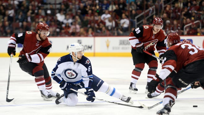 Dec 31, 2015; Glendale, AZ, USA; Winnipeg Jets center Alexander Burmistrov (6) passes the puck against the Arizona Coyotes during the first period at Gila River Arena. The Coyotes won 4-2.