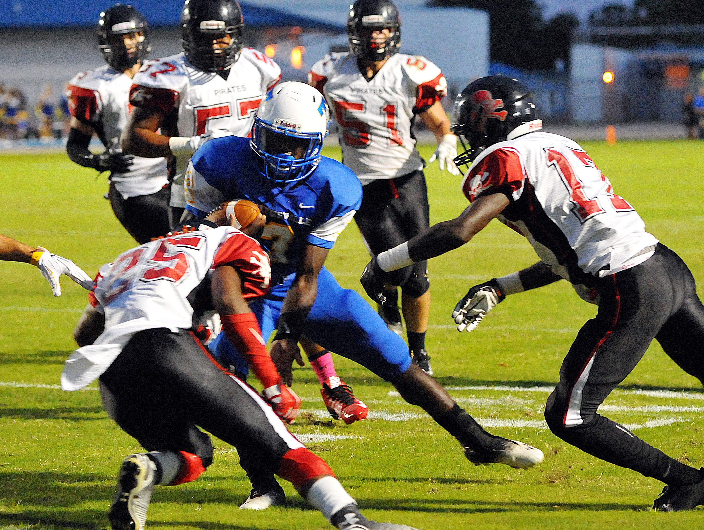 Titusville High's Dontavious Marcus (3) tries to avoid a host of Palm Bay high defenders during Friday night's game held at the Titusville High School football stadium.