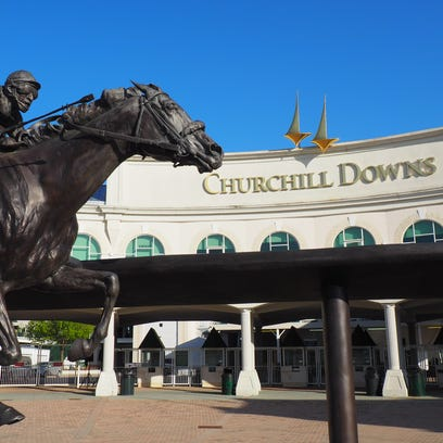 Churchill Downs behind a statue in memorial of Derby