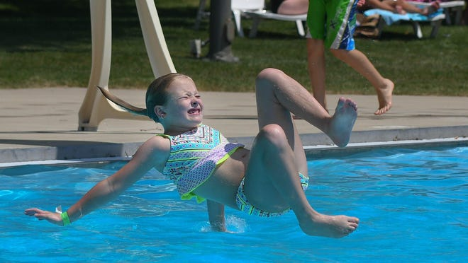 Second-grader Adalynn Crewse braces the entry on her flip attempt off the diving board at the Dogwood Pool, July 2, 2020. The pool reopened, with COVID-19 restrictions, July 1 just in time for a hot Independence Day holiday weekend.