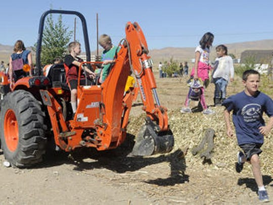 Students play on a piece of farm equipment at Silver