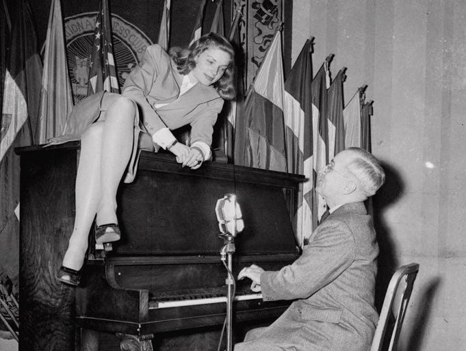 Vice President Harry S. Truman plays the piano as actress Lauren Bacall, perched on the instrument, looks on, at the National Press Club canteen in Washington, Feb. 10, 1945. Bacall has been a long-time devotee to the Democratic Party.