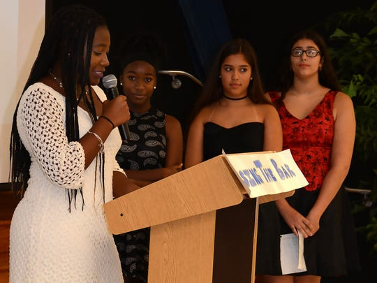 Top student Sade Bassin speaks to her classmates, family