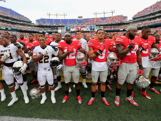 Members of the Navy Midshipmen and Ohio State Buckeyes stand together following the Buckeyes 34-17 win at M&T Bank Stadium on August 30, 2014 in Baltimore, Maryland.