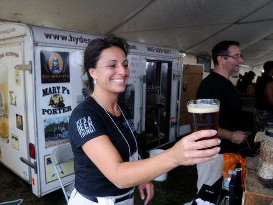 In this September 2014 file photo, Angela LoBianco-Barone of the Hyde Park Brewing Company hands over a freshly-poured pint to a customer at the Hudson Valley Wine & Food Fest in Rhinebeck.