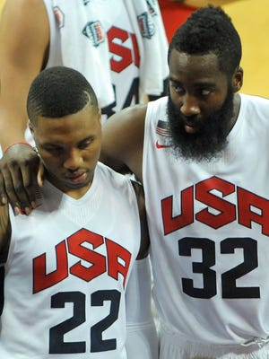 Team USA stars Damian Lillard, left, and James Harden look on as Paul George receives medical attention Friday.