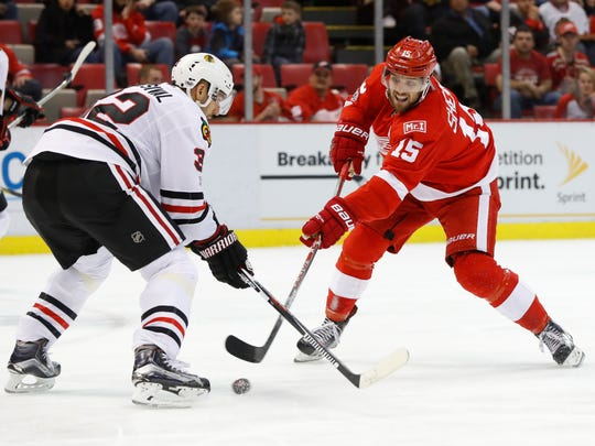 Red Wings center Riley Sheahan (15) shoots on Blackhawks defenseman Michal Rozsival (32) in the second period of the Wings' 4-2 win Friday at Joe Louis Arena.