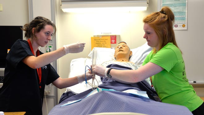 Camper Tori Gehling (left) practices administering medication through a nasogastric tube with the help of Allie Rein, a camp counselor, at Scrubs Camp on Monday.