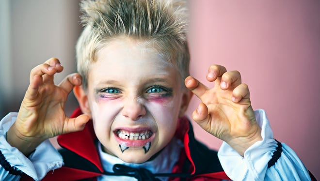 Portrait of a little boy dressed up as halloween vampire. The boy is aged 6 and is making scary face at the camera.