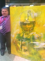Devin Argall, 14, of Manitowoc stands next to a painting of Green Bay Packers quarterback Aaron Rodgers done by performance artist Elliott From of Chicago at the second annual MDA Green Bay Muscle Team Gala at the Lambeau Field Atrium on Thursday night, June 23. Appleton couple Kurt and Donna Jacobson purchased the painting in a live auction at the event and later gifted the artwork to Argall, this year's MDA Wisconsin goodwill ambassador.