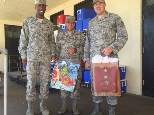 Staff Sergeant Frederick Scarber, left, and Senior Airmen Aldonys Reynoso and Nicholas Creighton, who deliver for Meals on Wheels every Wednesday, dropped off Reaching Out gifts on their Dec. 13 route. The men, stationed at Patrick Air Force Base, say volunteering has changed their lives and hopefully, the lives of those they meet.