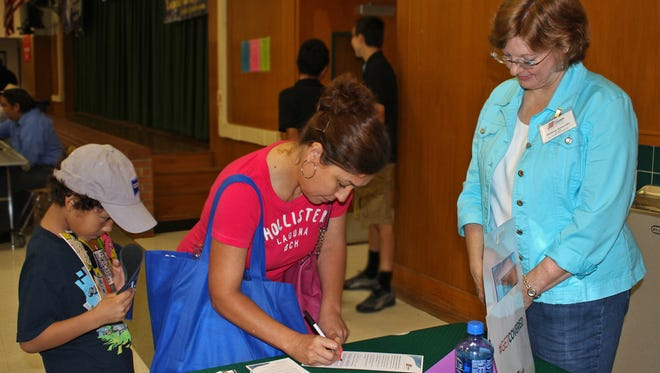 Get Covered America Field Organizer Deanne Zurovetz waits for a young woman to sign a form saying she plans to sign up for health insurance  at a fair hosted by Sul Ross Middle School in San Antonio in September.