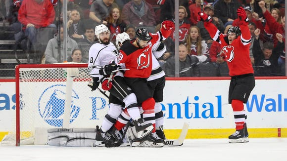 New Jersey Devils center Travis Zajac (19) scores a goal on Los Angeles Kings goalie Jonathan Quick (32) during the first period at Prudential Center.