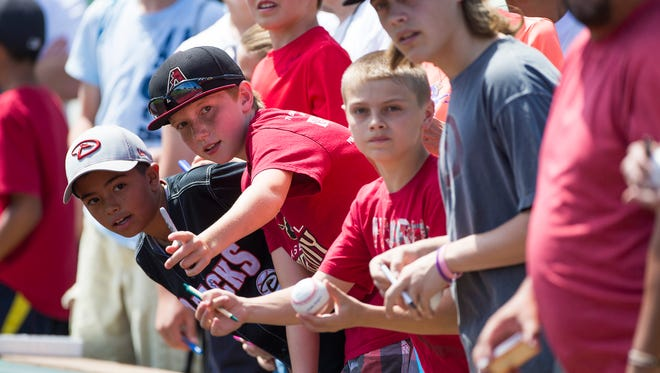 Arizona Diamondbacks fans look for autographs from players before a spring training game against the Los Angeles Dodgers at Salt River Fields at Talking Stick March 30, 2015.