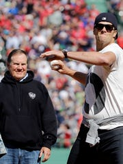 In this April 13, 2015, file photo, New England Patriots quarterback Tom Brady throws the ceremonial first pitch as Patriots coach Bill Belichick watches prior to the Boston Red Sox's home-opener baseball game against the Washington Nationals at Fenway Park in Boston.