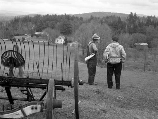 Historic photo shows Ascutney farmer Romaine Tenney, left, looking out over his land. He refused to sell his property to build I-91, but lost in court. When crews arrived to demolish his house, Tenney barricading himself in his house and set it on fire.