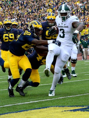 Spartans running back LJ Scott high-steps it into the end zone to get past a Michigan defender in the second quarter at Michigan Stadium, October 17, 2015 in Ann Arbor, Michigan.