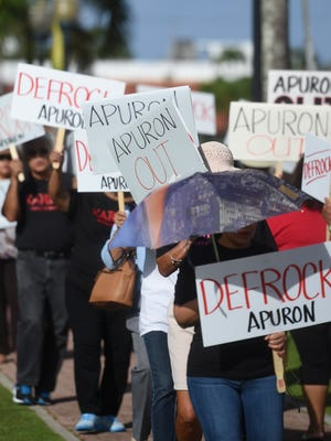 "In this Jan. 29 file photo, ""Defrock Apuron"" and ""Apuron Out"" signs in a picket line at the Dulce Nombre de Maria Cathedral-Basilica in Hagåtña."