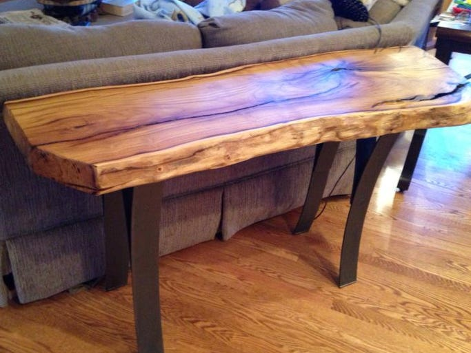A mulberry log table by Marc Rasmussen with custom metal legs.