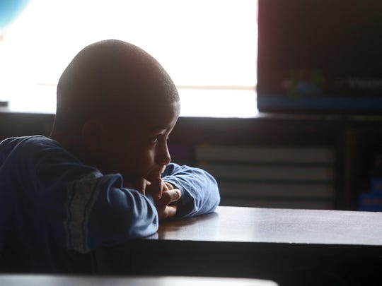 Jareil Bennett, a student at Museum School 25 in Yonkers, sits in a darkened class. On warm days, some teachers will leave the lights off to keep the classrooms from getting too hot. The district has one guidance counselor for every 827 students, one social worker for every 2,405, and one librarian for every 3,307.