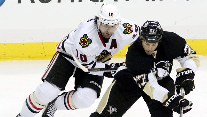Chicago Blackhawks left wing Patrick Sharp (10) and Pittsburgh Penguins right wing Craig Adams (27) chase the  puck during the second period at the CONSOL Energy Center.