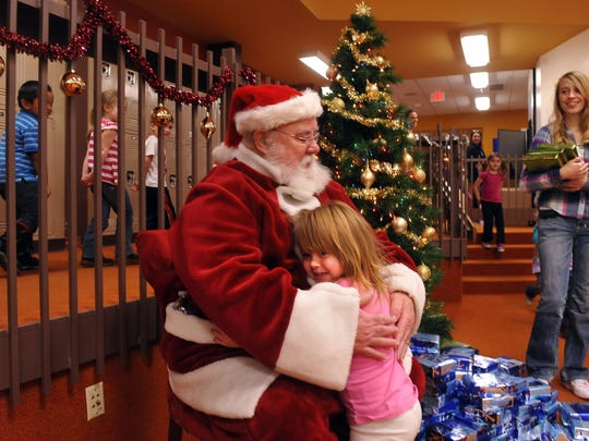 A girl hugs Santa during the Great Falls Kiwanis Club Christmas party for the Skyline Early Learning Center. This year the club will put on the 56th annual party for Skyline kids. TRIBUNE PHOTO/RION SANDERS