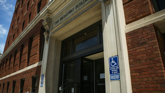 A handicap sign tacked to the wall outside of the Hamilton County Board of Elections building on Broadway redirects disabled visitors to the rear entrance for parking. The front entrance has a wheelchair lift that allows access to the building.