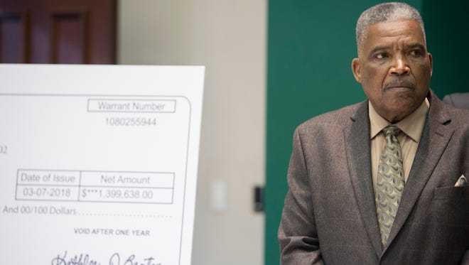 Robert Porterfield, MCBOE president, looks on during a press conference on Monday, March 12, 2018 at the AEA in Montgomery, Ala., while standing in front of a print out of a check representing approximately $1.4 million that was returned to the Montgomery County School System from the State of Alabama in court.