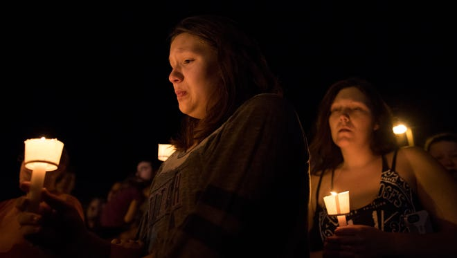 A girl becomes emotional during a vigil kept across the street from the First Baptist Church of Sutherland Springs where 26 people were killed in shooting Sunday, Nov. 5, 2017, in Sutherland Springs.