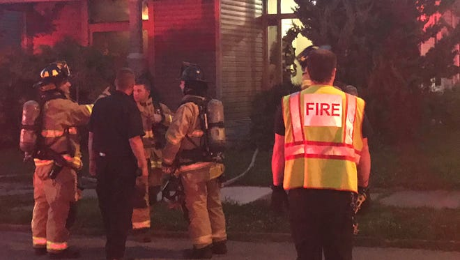 Newark firefighters talk to assistant chief John Clouse on Saturday evening after extinguishing a fire on W. Locust Street.