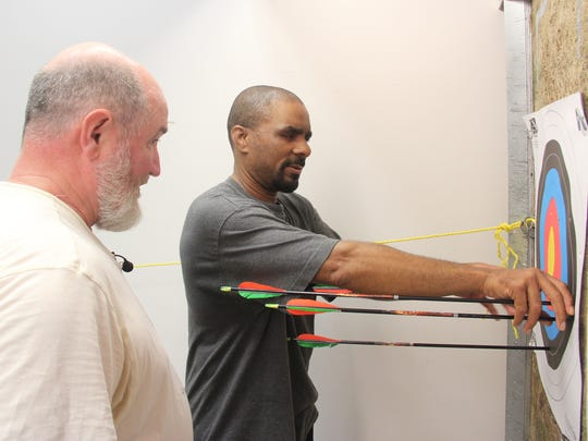 Anthony Hicks pulls arrows he shot from a target as