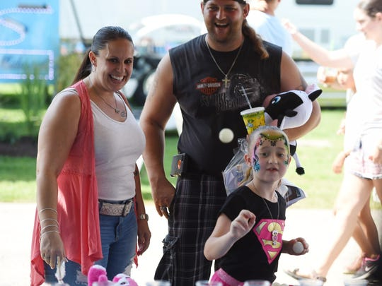 Makaylah Kelleher of Pleasant Valley attempts to get a ping-pong ball into a fish bowl at the Dutchess County Fair on Saturday. Her mother Bernadette Kelleher and Chuck Bouton cheer her on.