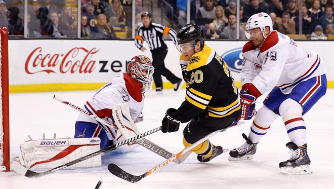 Jan 30, 2014; Boston, MA, USA;  Boston Bruins left wing Daniel Paille (20) shoots the puck against Montreal Canadiens goalie Peter Budaj (30) as defenseman Andrei Markov (79) chases during the third period at TD Banknorth Garden. The Montreal Canadiens won 4-1.