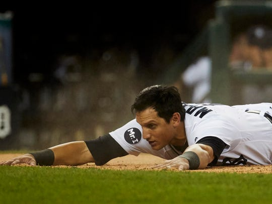 Tigers centerfielder Mikie Mahtook (15) dives in safe