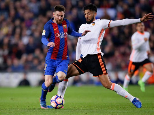 FC Barcelona's Lionel Messi, left, duels for the ball with Valencia's Ezequiel Garay during the Spanish La Liga soccer match between FC Barcelona and Valencia at the Camp Nou stadium in Barcelona, Spain, Sunday, March 19, 2017. (AP Photo/Manu Fernandez)