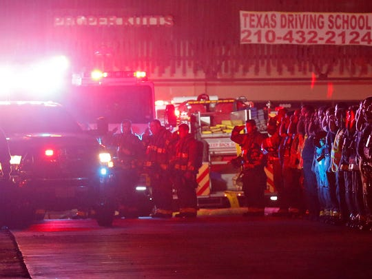 San Antonio firefighters salute an ambulance carrying