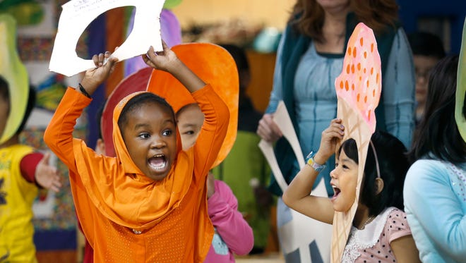 "Hawa Ali next to Tashi Dema take part with other first-graders in their performance of ""The Hungry Caterpillar"" at a morning briefing at Children's School of Rochester (School 15)."