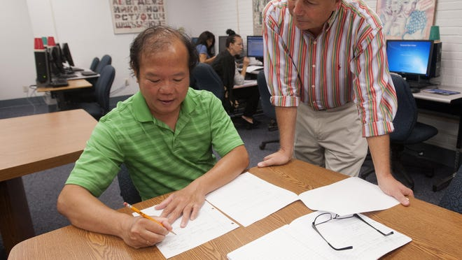 Pensacola State College student, Quang Pham, left, gets help with a developmental writing assignment from instructor Edward Pate during class at PSC Wednesday morning June 24, 2015.
