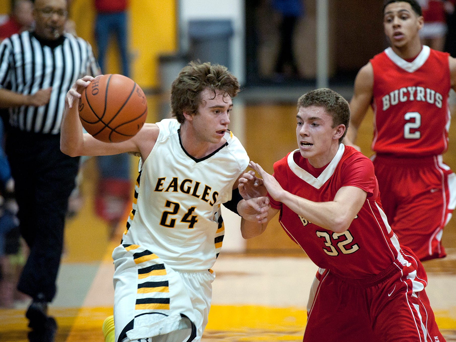Colonel Crawford's Todd Entenmann runs down the court while under pressure from Bucyrus' Paul Holdcraft earlier this season. The Eagles grabbed the top seed in the Division III Ashland District Super Sectional on Sunday afternoon.
