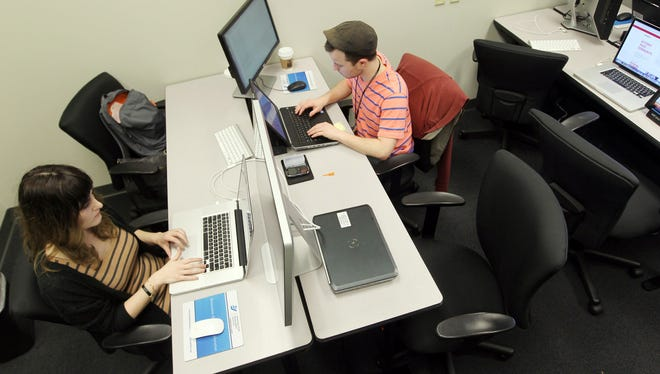 Northern Kentucky University students Rebecca Schneider (left), a senior studying visual communication, and Wayne Leeky, a sophomore studying computer information technology, work in NKU's center for applied informatics RiverCenter lab in a Corporex Tower, Covington.