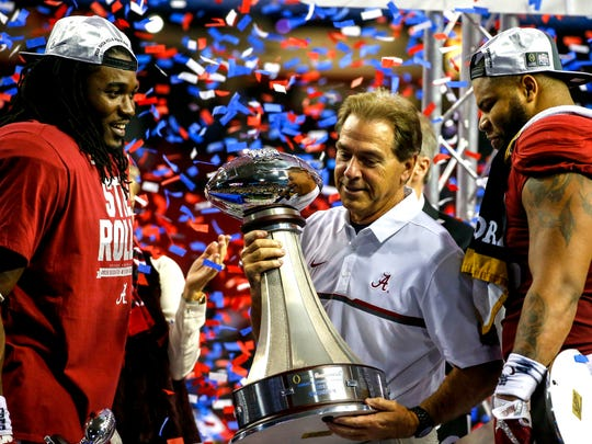 Alabama head coach Nick Saban holds up the trophy with running back Bo Scarbrough (9) left, and linebacker Ryan Anderson (22) right, after they defeated Washington 24-7 in the Peach Bowl NCAA college football game, Saturday, Dec. 31, 2016, in Atlanta.