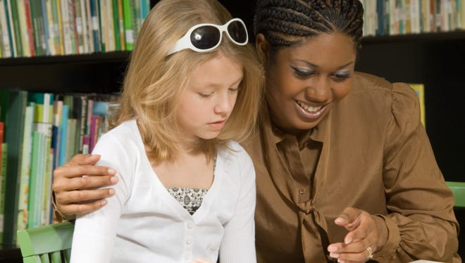Woman training girl for literacy work