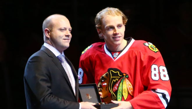 Chicago Blackhawks general manager Stan Bowman presents right wing Patrick Kane (right) with a golden puck to commemorate Kane's 26-game point streak prior to a game against the Ottawa Senators at the United Center.