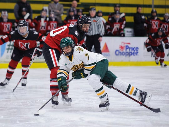 Catamount forward Kristina Shanahan (7) is tripped up in front of the Northeastern bench during the women's hockey game between the Northeastern Huskies and the Vermont Catamounts at Gutterson Fieldhouse on Friday night January 26, 2018 in Burlington.