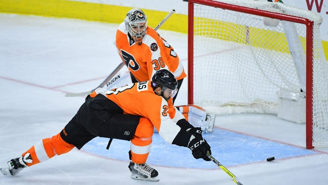 Goalies Michal Neuvirth, center, and Steve Mason could use a little help as they try to improve their own play.