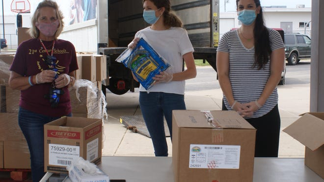 In this June file photo, Cindy Long (left), Haley McClain (center), and Kaitlyn Gudzinskas, all of Pekin, unpack boxes for distribution at a mobile food pantry hosted earlier this month.