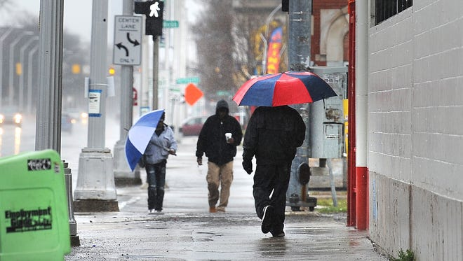 People protect themselves from the rain  on Saturday Woodward Avenue near Elmhurst.  Freezing rain is expected to start as early as 6 p.m., but will be most harsh overnight into Sunday, said Alex Manion, a meteorologist with the National Weather Service in White Lake Township.