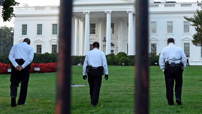 Uniformed Secret Service officers walk along the lawn on the North side of the White House in Washington on Saturday.