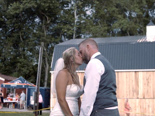 Bethany and Todd Snowden kiss outside the barn they have been building that will begin housing the Creekside Occasions wedding and events center this fall. Their wedding Saturday gave them more insight as to how their business should be arranged inside the barn.