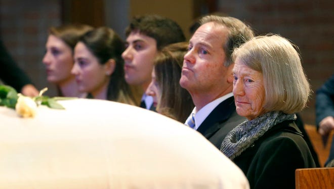 An emotional Elaine Costello, next to her son Brett, glances at the casket with her deceased husband Anthony during the funeral at St. Louis Church.